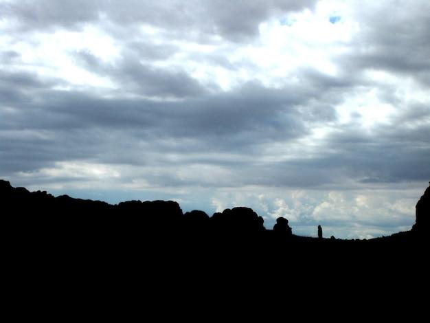 Image de gros rochers silhouettés sur un ciel gris et nuageux avec du soleil qui brille à travers