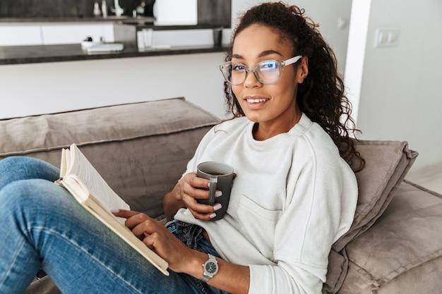 Image de happy african american girl reading book et boire du thé, assis sur un canapé en appartement lumineux