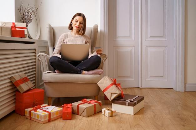 Image de happy nice woman holding carte de crédit avec copie espace à l'aide d'un ordinateur portable