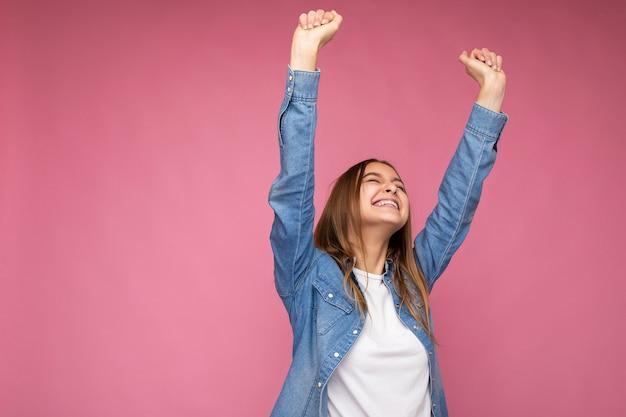 Image heureuse de la belle jeune femme blonde foncée avec des émotions sincères isolées sur le mur de fond