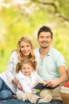 Image d'heureuse jeune famille ayant pique-nique en plein air.