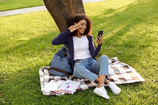 Image de l'heureuse jeune femme africaine assise à l'extérieur dans le parc à l'aide d'un téléphone mobile, écouter de la musique avec des écouteurs faire selfie avec un geste de paix.