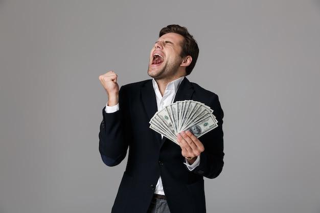 Image d'heureux homme d'affaires de 30 ans en costume souriant et tenant un ventilateur d'argent en billets en dollars, isolé sur mur gris