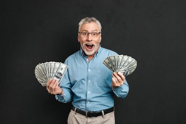 Image d'un homme adulte joyeux des années 60 aux cheveux gris tenant de l'argent deux fans de billets de 100 dollars et hurlant de bonheur, isolé sur mur noir