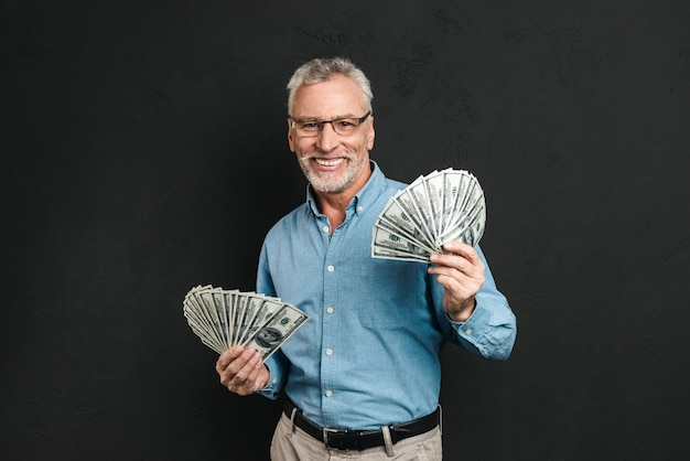 Image d'un homme adulte riche et beau des années 60 aux cheveux gris tenant de l'argent deux fans de billets de 100 dollars et se réjouissant de sa richesse, isolé sur un mur noir