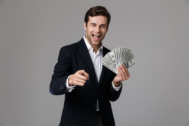 Image de l'homme d'affaires des années 30 en costume souriant et tenant fan d'argent en billets en dollars, isolé sur mur gris