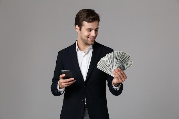 Image d'homme d'affaires des années 30 en costume tenant fan d'argent en billets en dollars et smartphone, isolé sur mur gris