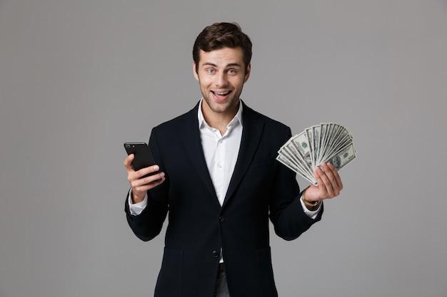 Image d'homme d'affaires des années 30 en costume tenant fan de dollars et smartphone, isolé sur mur gris
