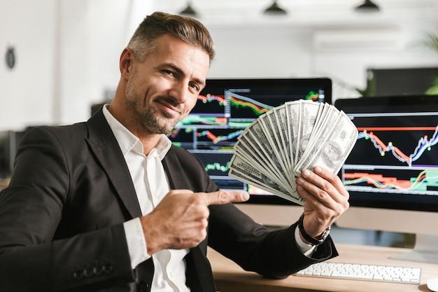Image d'homme d'affaires attrayant de 30 ans portant costume tenant un ventilateur d'argent tout en travaillant au bureau avec des graphiques et des tableaux sur ordinateur
