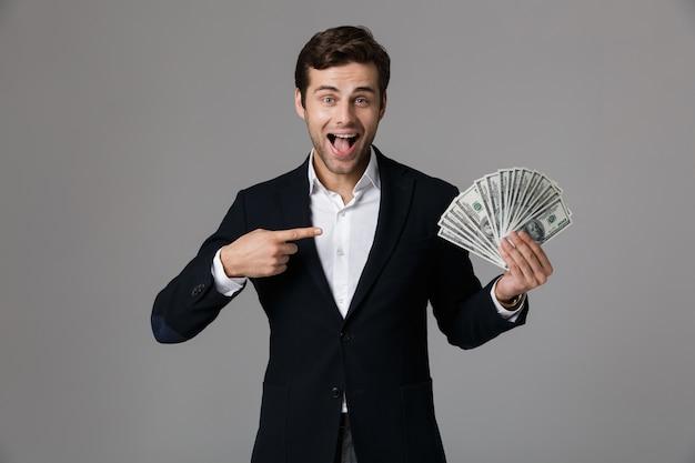 Image d'homme d'affaires caucasien des années 30 en costume souriant et tenant fan d'argent en billets en dollars, isolé sur mur gris