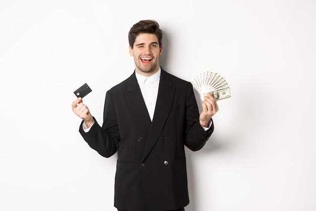 Image d'un homme d'affaires confiant en costume noir, souriant heureux et faisant un clin d'œil, tenant de l'argent et une carte de crédit, debout sur fond blanc.