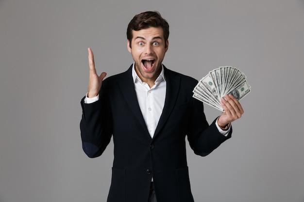 Image d'homme d'affaires positif de 30 ans en costume souriant et tenant un ventilateur d'argent en billets en dollars, isolé sur mur gris