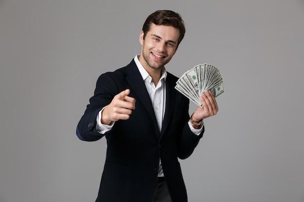 Image d'homme d'affaires prospère des années 30 en costume souriant et tenant fan d'argent en billets en dollars, isolé sur mur gris