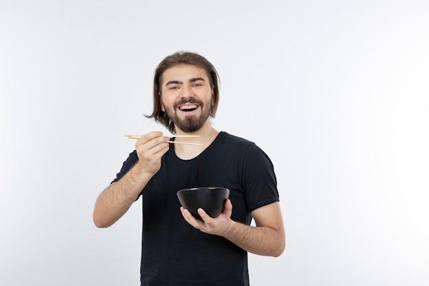 Image d'homme barbu tenant un bol avec des baguettes sur un mur blanc.