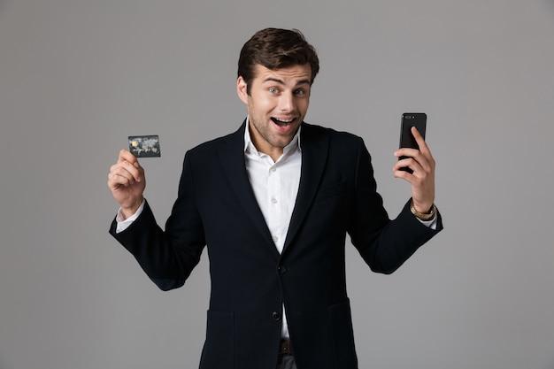 Image de l'homme brune des années 30 en costume d'affaires tenant un téléphone mobile noir et une carte de crédit, isolé sur mur gris