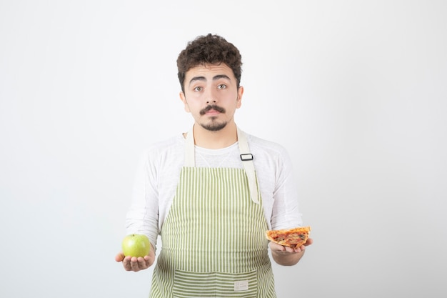 Image d'un homme cuisinier tenant une pizza et une pomme verte sur blanc