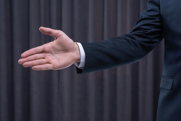 Image d'un homme élégant en costume tendant la main pour une poignée de main. concept d'entreprise. technique mixte