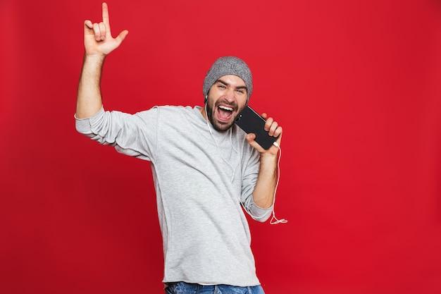 Image de l'homme européen 30s chantant tout en écoutant de la musique avec des écouteurs et un téléphone mobile, isolé