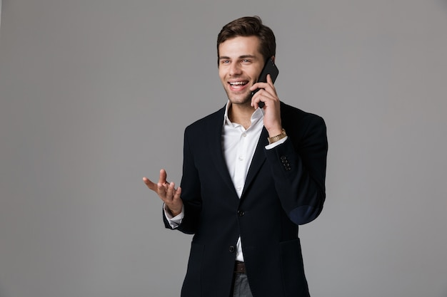 Image de l'homme heureux des années 30 en costume d'affaires parlant sur smartphone noir, isolé sur mur gris