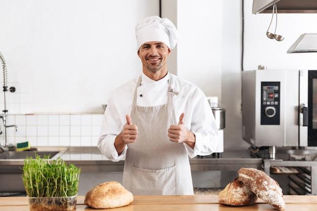Image de l'homme heureux boulanger en uniforme blanc souriant, debout à la boulangerie avec du pain sur la table