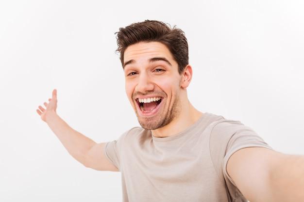 Image d'un homme heureux en t-shirt décontracté et à poils sur le visage se réjouissant et prenant selfie avec sourire, isolé sur mur blanc