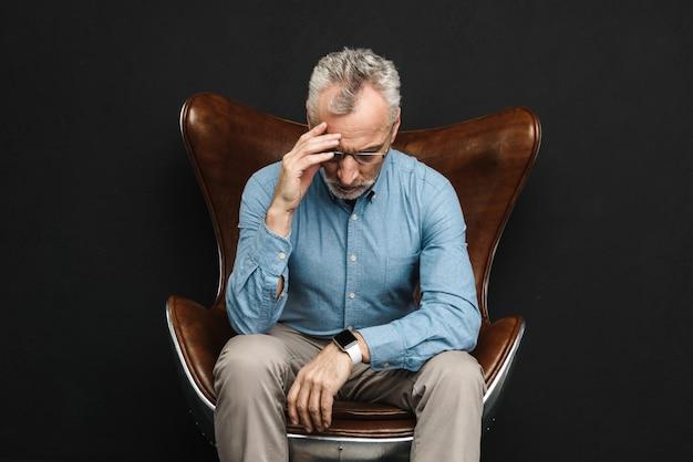 Image de l'homme intelligent des années 50 ayant les cheveux gris et la barbe dans des verres assis sur un fauteuil professionnel avec le visage vers le bas, isolé sur un mur noir