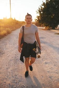 Image d'un homme avec longboard sur route