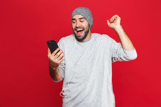 Image d'un homme non rasé de 30 ans en tenue décontractée tenant un téléphone portable et écouter de la musique avec des écouteurs isolés