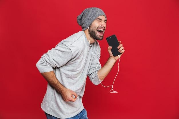 Image de l'homme non rasé 30s chantant tout en écoutant de la musique avec des écouteurs et un téléphone mobile, isolé