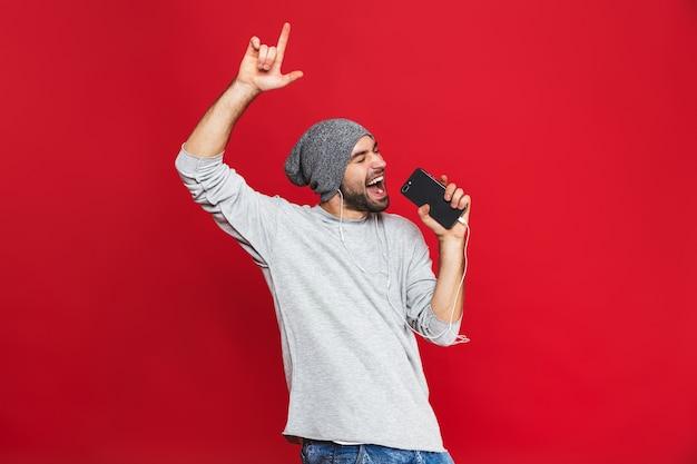 Image de l'homme optimiste 30s chantant tout en écoutant de la musique avec des écouteurs et un téléphone mobile, isolé
