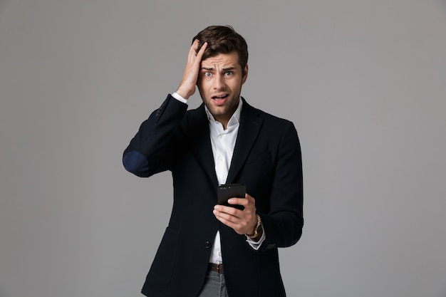 Image de l'homme perplexe 30 en costume d'affaires à l'aide de smartphone noir, isolé sur mur gris