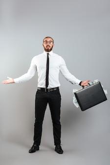 Image d'homme perplexe entrepreneur dans des verres et costume d'affaires jetant les mains avec un diplomate plein d'argent dollar, isolé sur mur gris