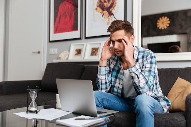Image d'un homme à poils stressant avec des maux de tête vêtu d'une chemise dans une impression de cage assis sur un canapé à la maison et utilisant un ordinateur portable