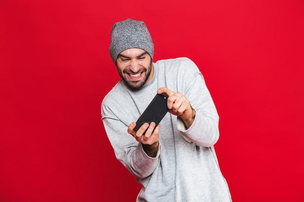 Image d'un homme positif de 30 ans tenant un smartphone et jouant à des jeux vidéo, isolé