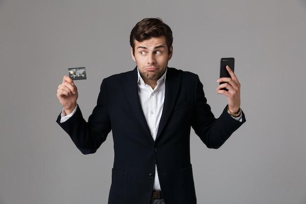 Image de l'homme de race blanche 30 en costume d'affaires tenant un téléphone portable noir et une carte de crédit, isolé sur mur gris