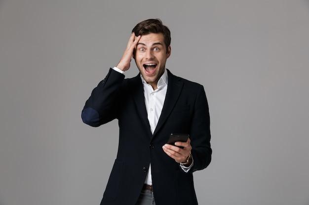 Image de l'homme ravi des années 30 en costume d'affaires à l'aide de téléphone mobile noir, isolé sur mur gris