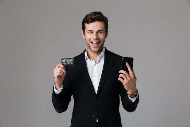 Image de l'homme ravi des années 30 en costume d'affaires tenant un téléphone mobile noir et une carte de crédit, isolé sur mur gris