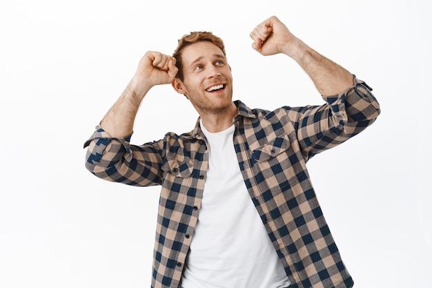 Image d'un homme roux heureux dansant et regardant le texte promotionnel dans le coin supérieur droit, s'amusant, faisant la fête et faisant la danse de la victoire, mur blanc