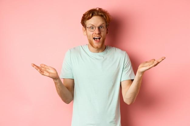 Image d'un homme roux surpris dans des lunettes écartant les mains sur le côté et semblant impressionné debout au-dessus de ...