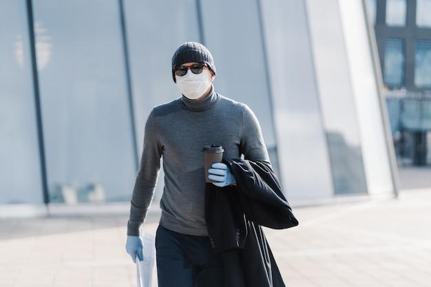 Image d'un homme sérieux qui se rend au travail, porte un chapeau, des lunettes de soleil, boit du café pour aller, tient un journal, évite la place publique pendant la période de quarantaine, pose en plein air. covid-19, concept de virus. grippe