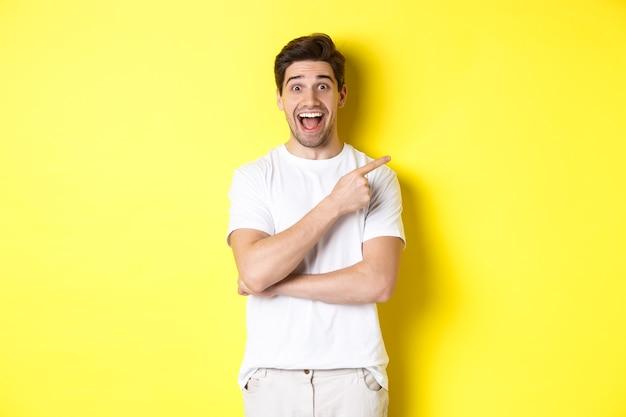 Image d'un homme souriant excité montrant des offres de vendredi noir, pointant le doigt vers la droite et regardant étonné, debout sur fond jaune.
