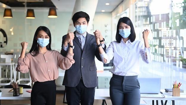 Image d'hommes d'affaires confiants ou d'employé de bureau portant un masque médical en se tenant debout dans un bureau moderne.