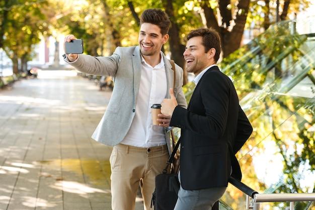 Image d'hommes d'affaires européens en costume à l'aide de smartphone tout en marchant en plein air à travers le parc verdoyant avec du café à emporter, pendant la journée ensoleillée