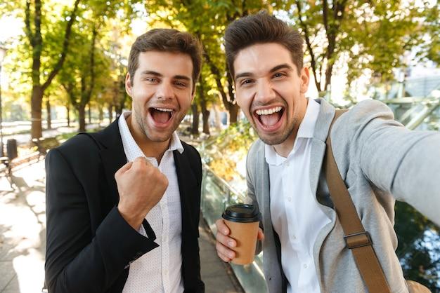 Image d'hommes d'affaires joyeux en costume prenant selfie photo sur téléphone portable, tout en marchant en plein air à travers le parc verdoyant avec du café à emporter