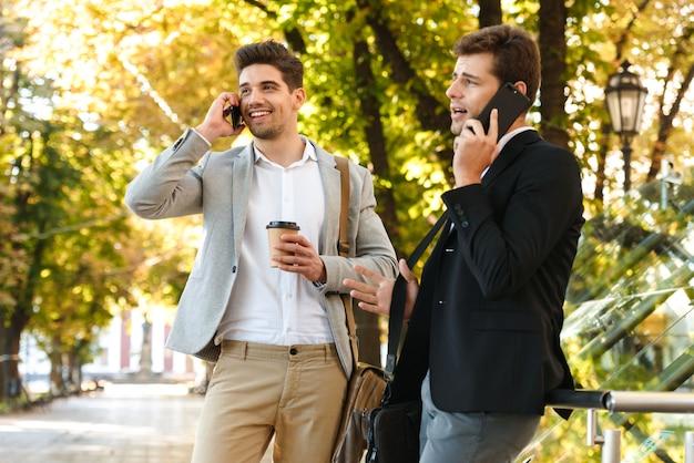 Image d'hommes d'affaires de race blanche en costumes à l'aide de smartphone tout en marchant en plein air à travers le parc verdoyant avec du café à emporter, pendant la journée ensoleillée