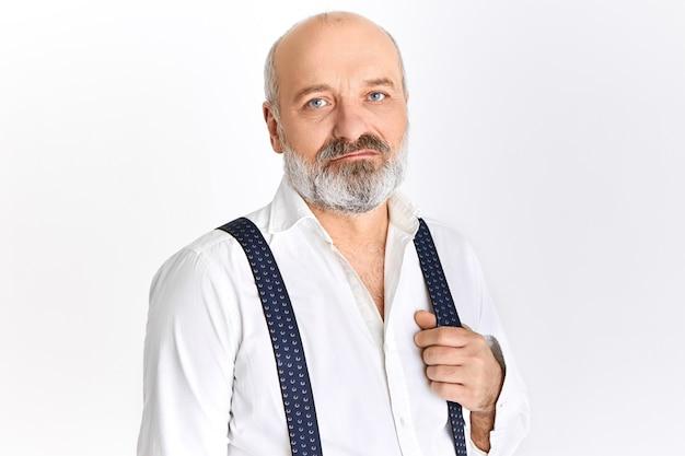 Image horizontale de l'attrayant homme à la retraite barbu sérieux avec tête chauve et visage ridé posant isolé sur fond de mur blanc, tirant une sangle de bretelles, ayant l'air confiant