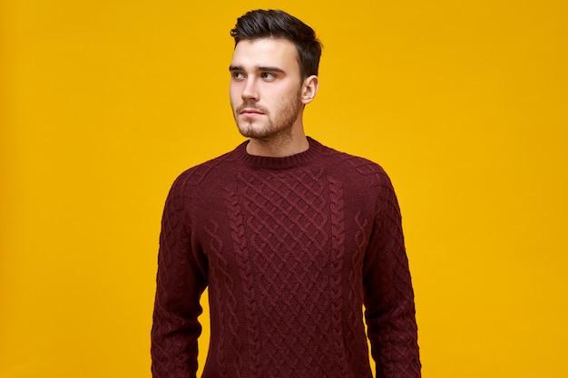 Image horizontale de l'attrayant jeune homme caucasien mal rasé aux cheveux noirs habillé en pull chaud tricoté sensation de froid le jour d'hiver, à la recherche de côté, posant isolé. concept de personnes et de style de vie