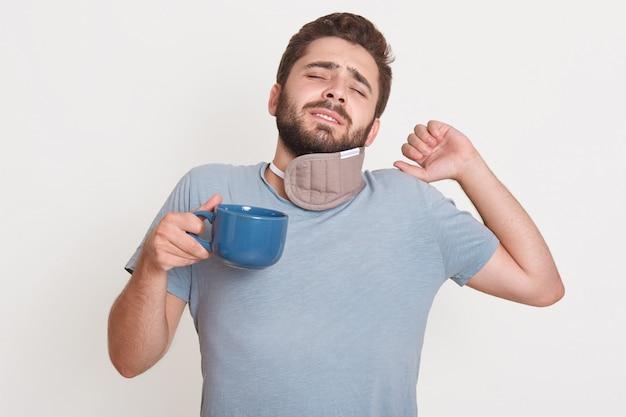 Image horizontale de l'homme barbu fatigué debout isolé sur mur blanc, fermant les yeux, levant une main, ayant un mauvais sommeil