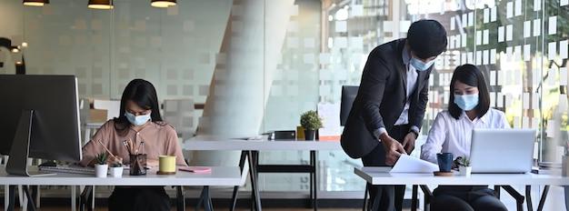 Image horizontale d'hommes d'affaires ou d'employé de bureau portant un masque médical tout en travaillant dans un bureau moderne.