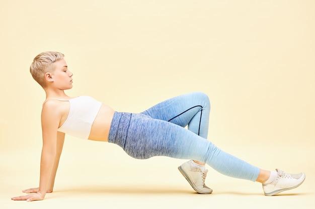 Image horizontale de jolie jeune femme de race blanche avec un corps athlétique et une formation de coiffure garçon dans une salle de sport faisant purvottanasana ou planche inversée pose planche avec les mains, la jambe sur le sol, pliant un genou